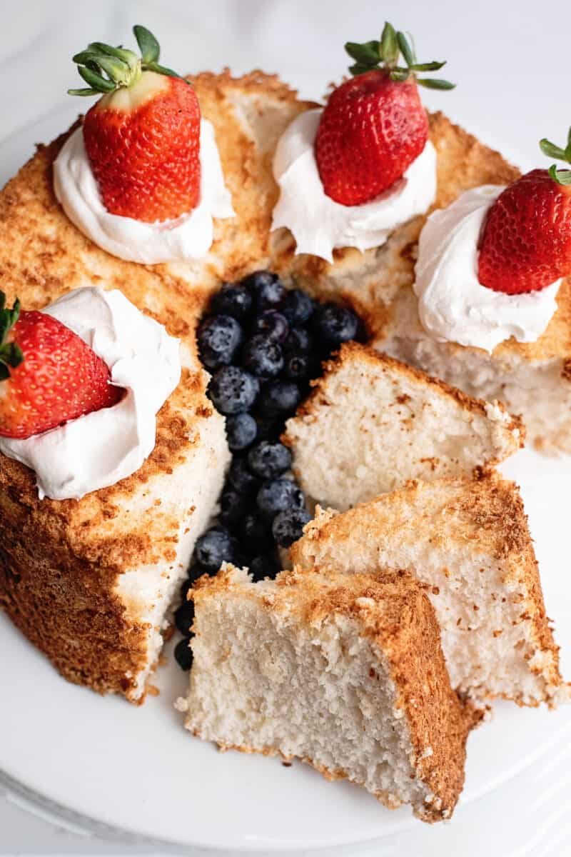 angel food cake sliced and topped with cream and berries