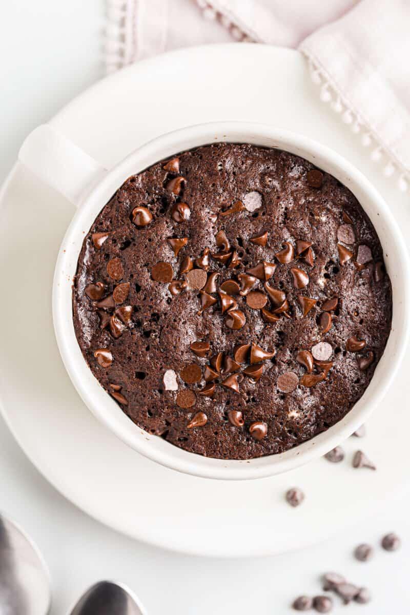overhead chocolate mug cake with chocolate chips in white mug