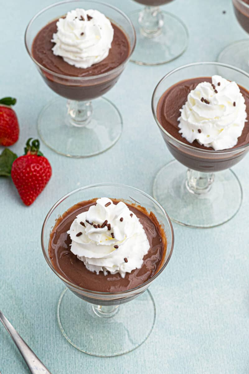 chocolate pudding topped with whipped cream in cups