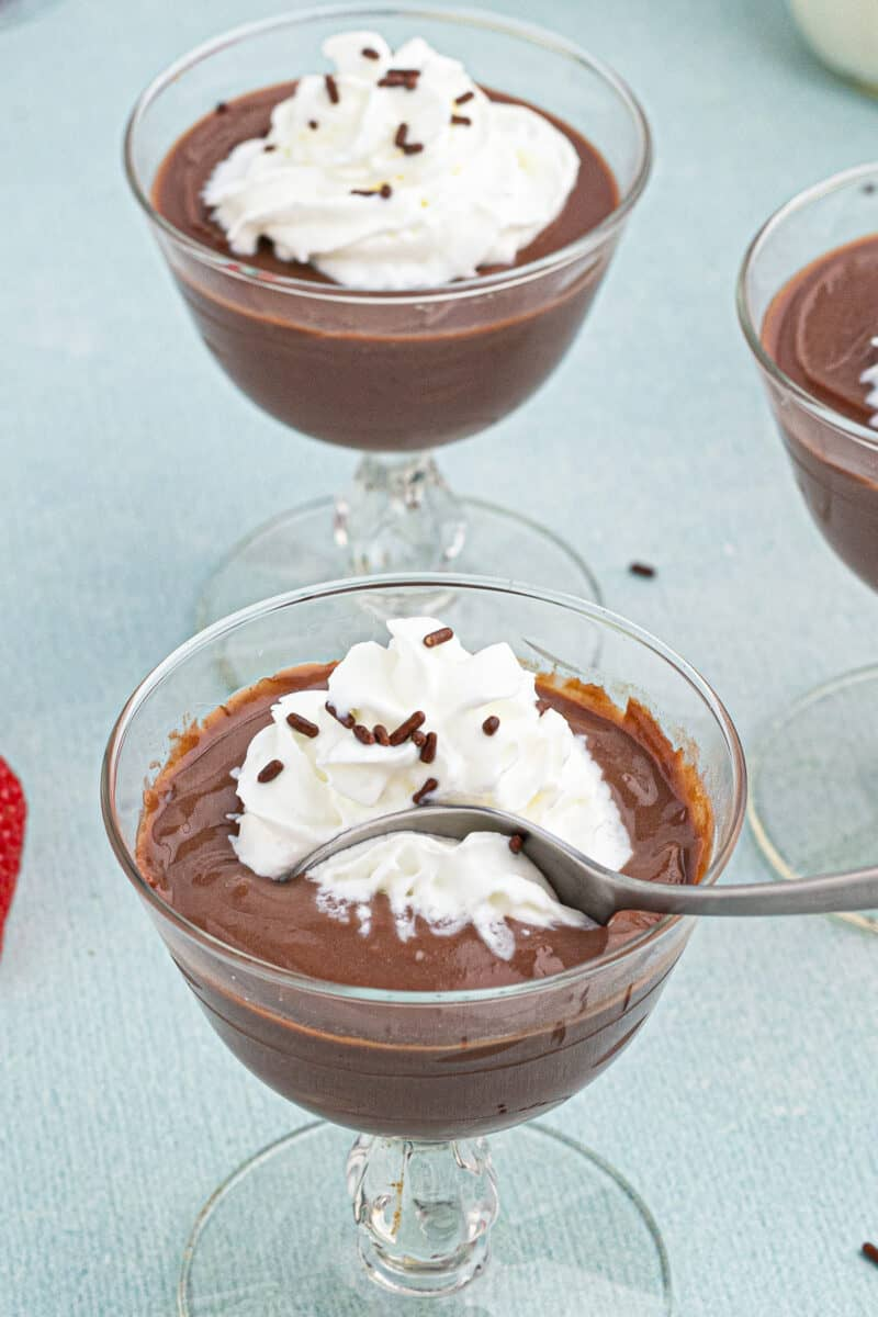 spoon digging into homemade chocolate pudding topped with whipped cream