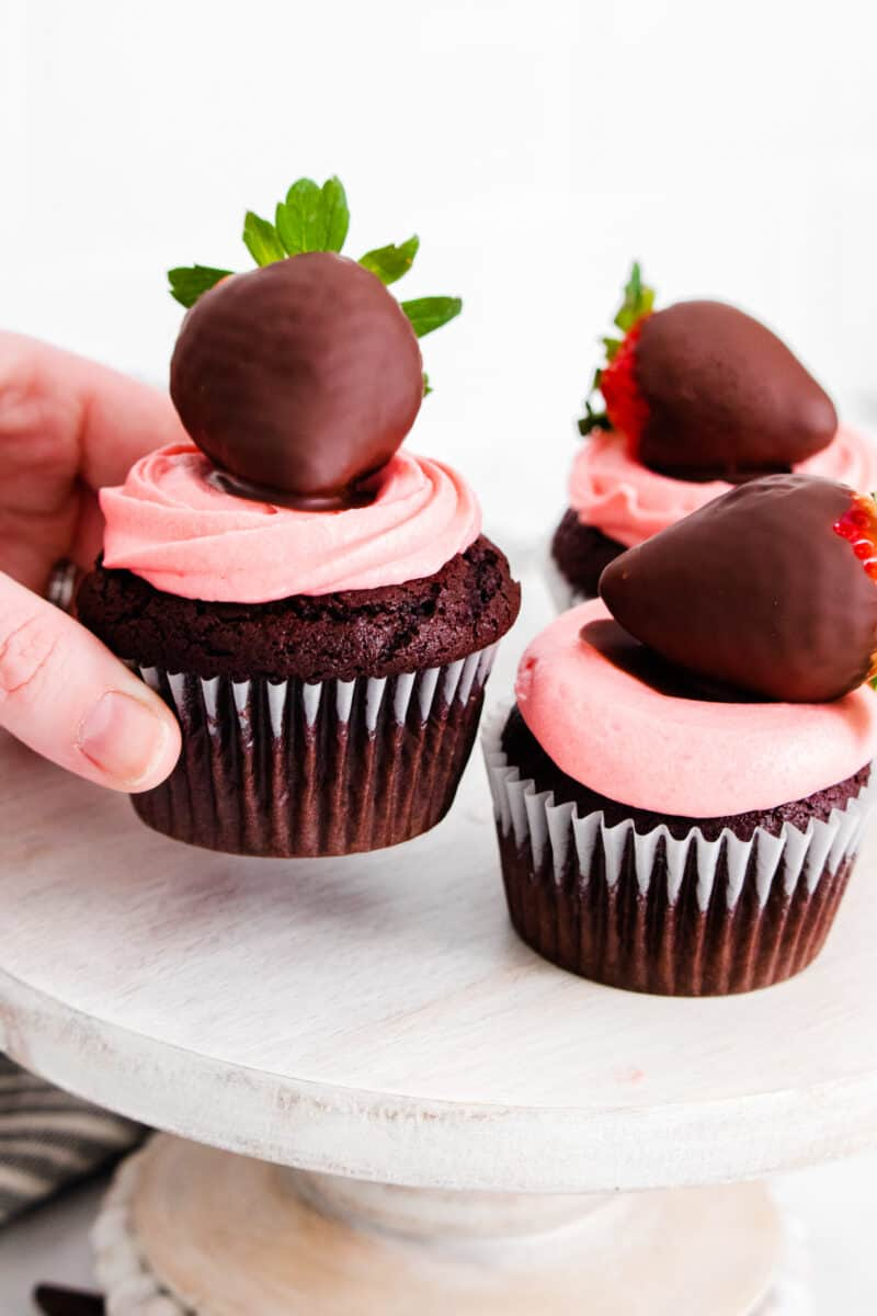 picking up chocolate covered strawberry cupcakes from cake stand