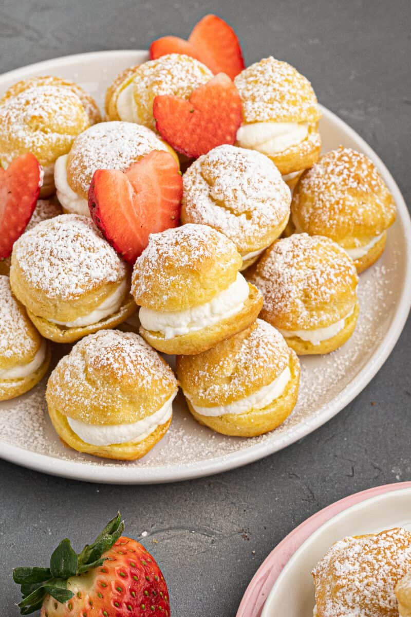 plate with cream puffs dusted in powdered sugar