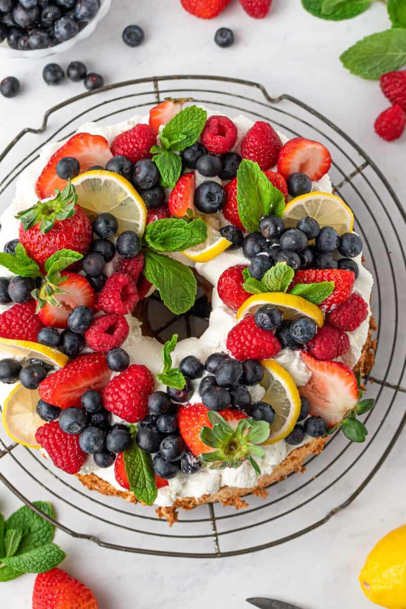 lemon angel food cake garnished with whipped cream and fruit