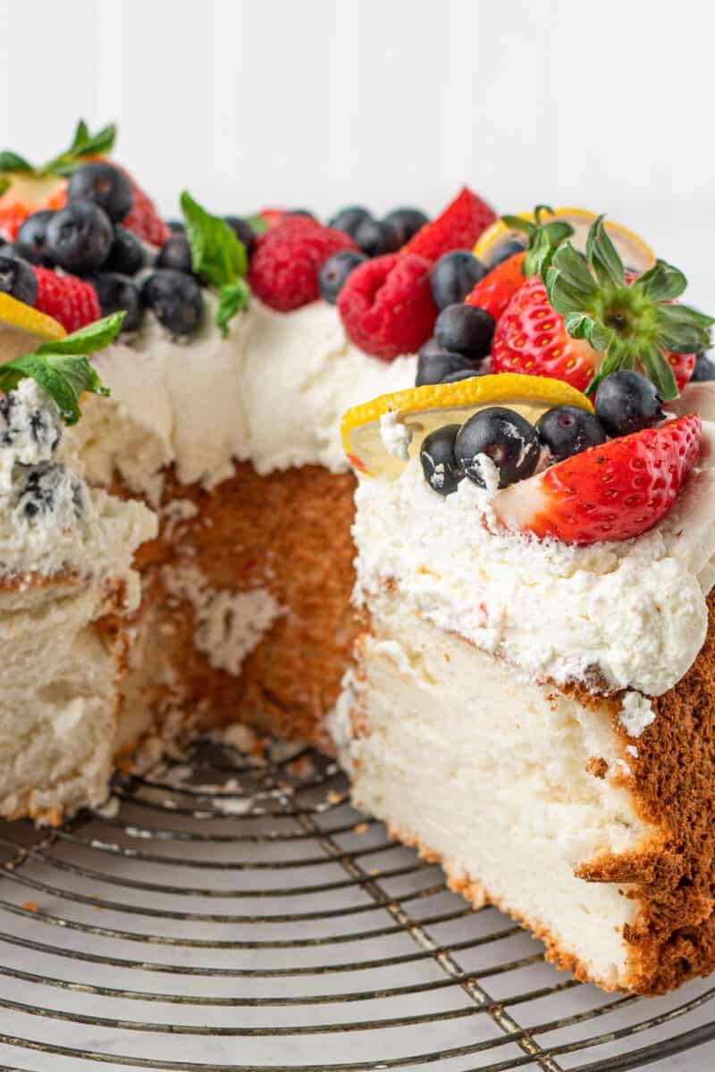 sliced lemon angel food cake garnished with whipped cream and fruit