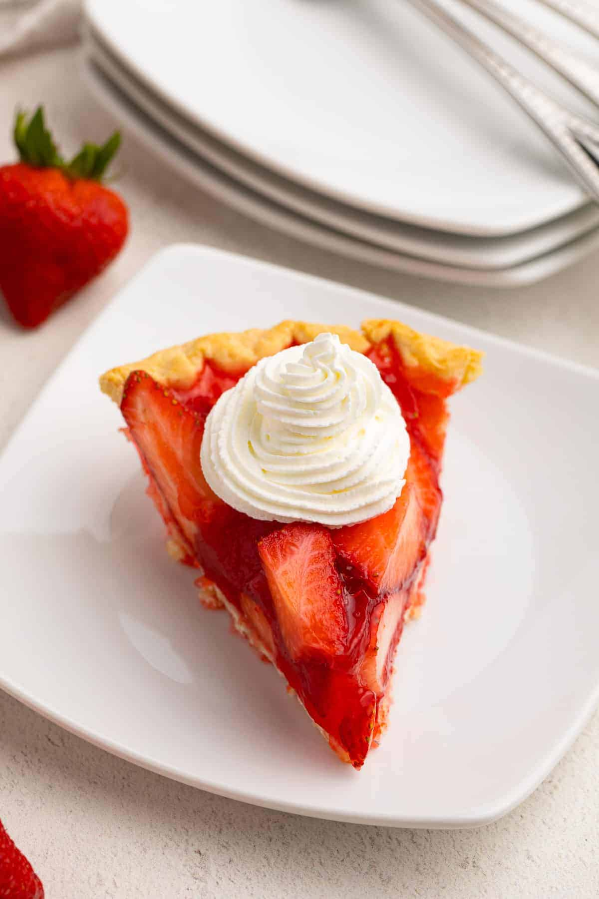 slice of strawberry jello pie with whipped cream on white plate