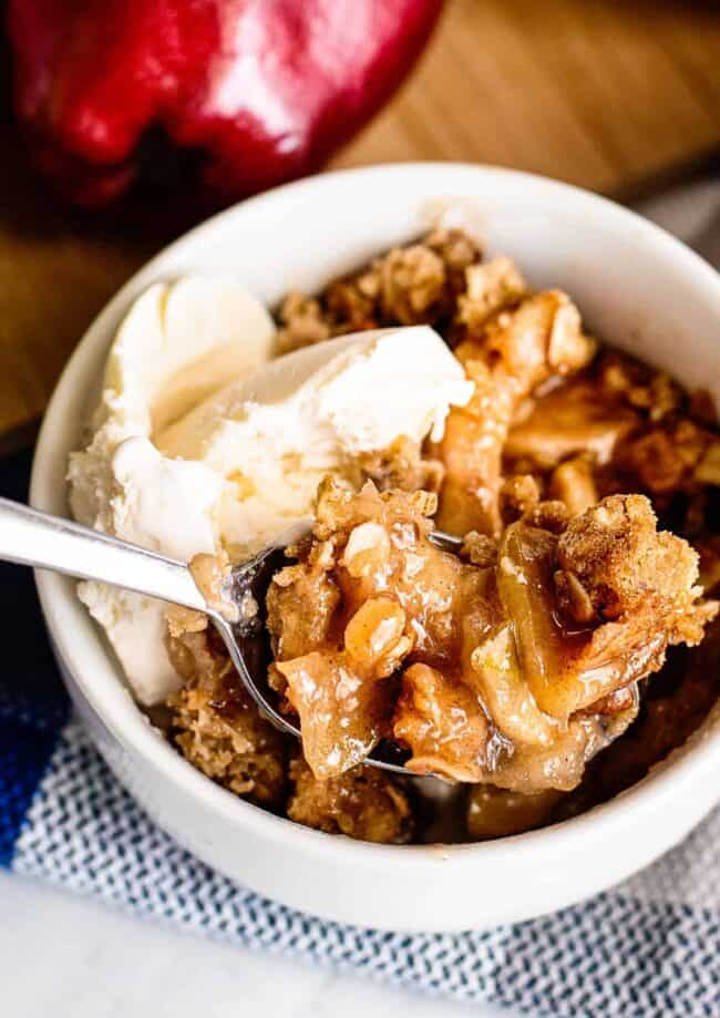 apple crisp with vanilla ice cream in white bowl
