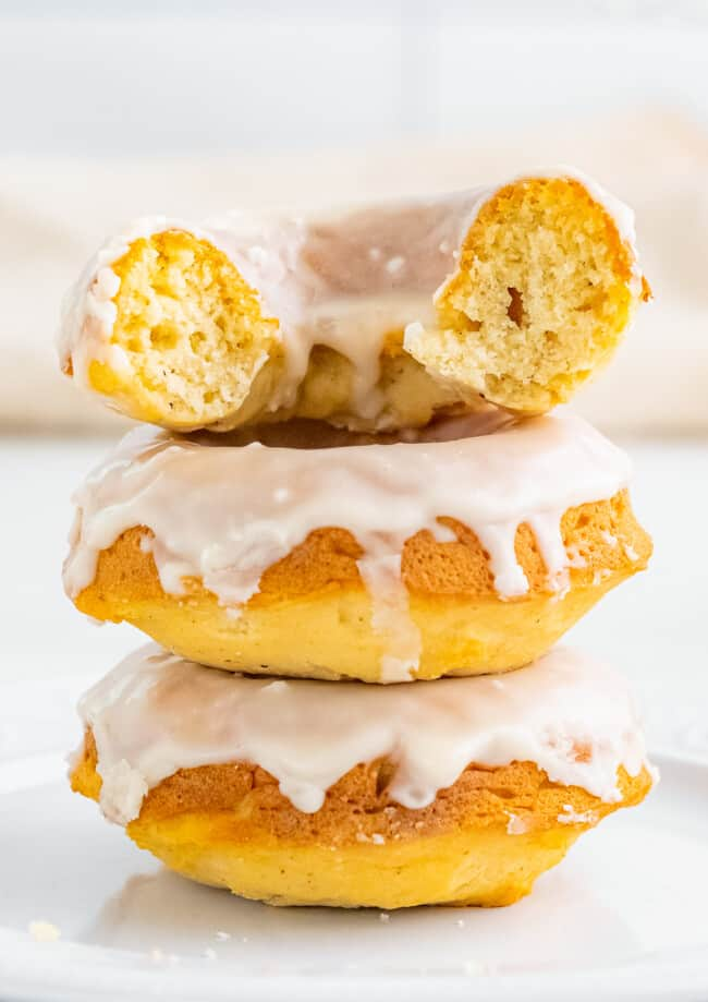 bite out of vanilla glazed baked donuts. three donuts stacked.