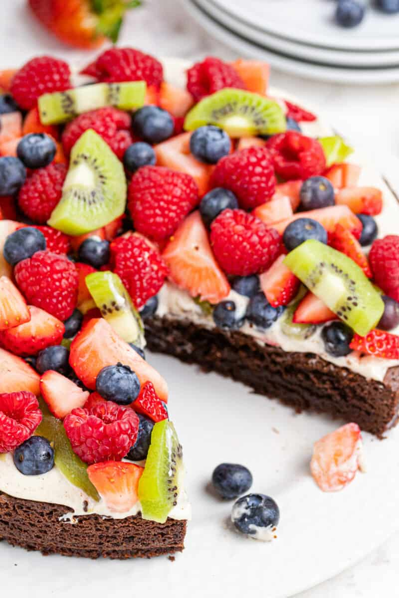 brownie fruit pizza topped with cream and sliced fruit