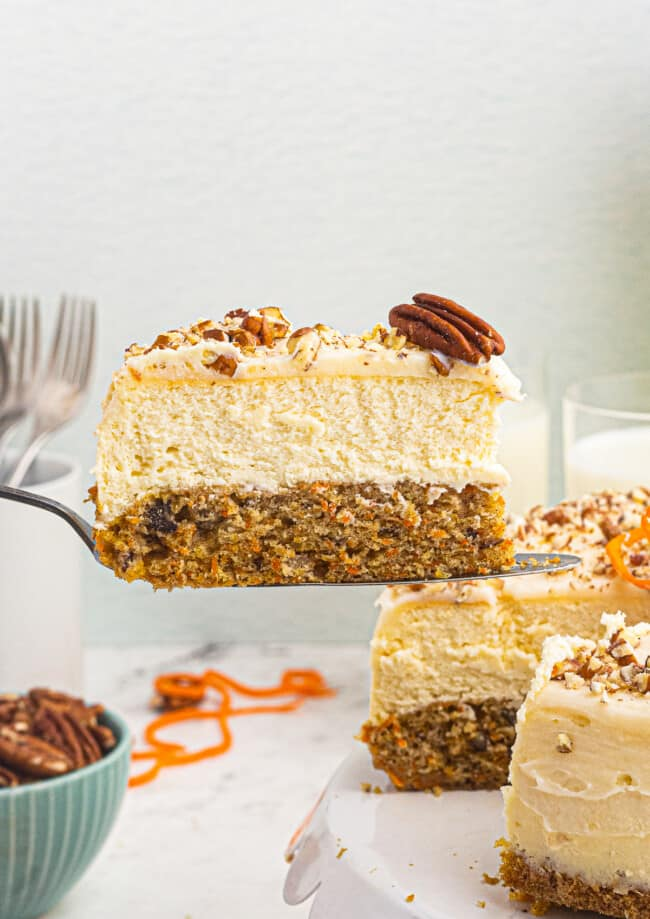 lifting up slice of carrot cake cheesecake