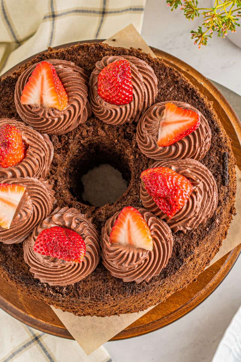 overhead photo of chocolate angel food cake with chocolate whipped cream frosting and strawberries