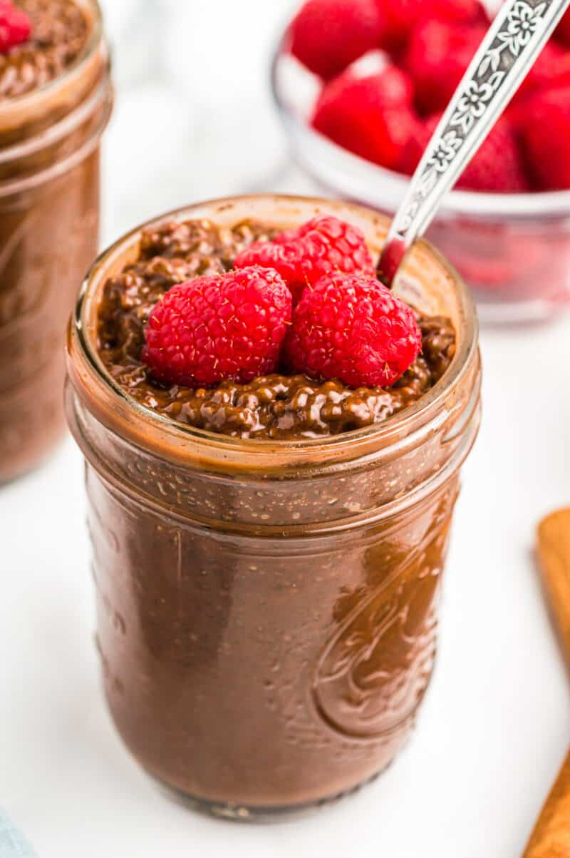 two jars of chocolate chia pudding garnished with raspberries