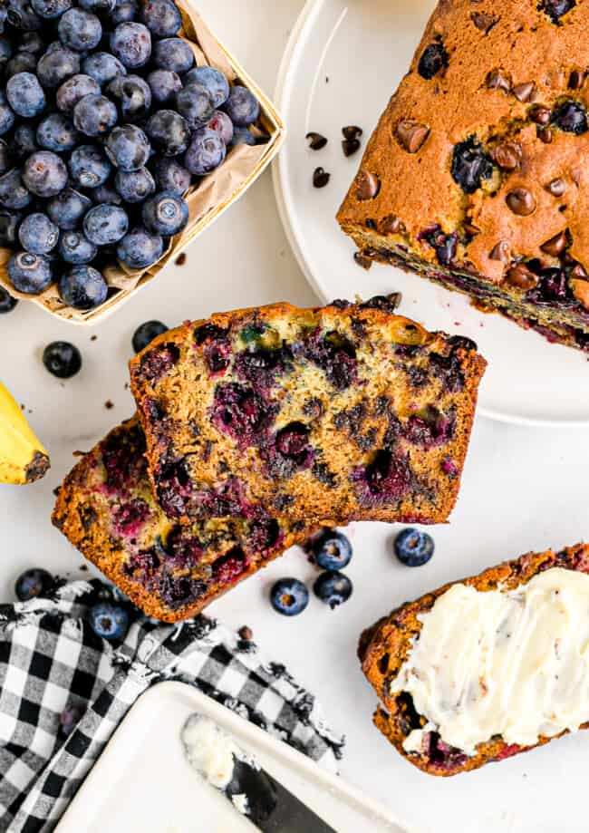 two stacked slices of chocolate chip blueberry banana bread on table next to blueberries