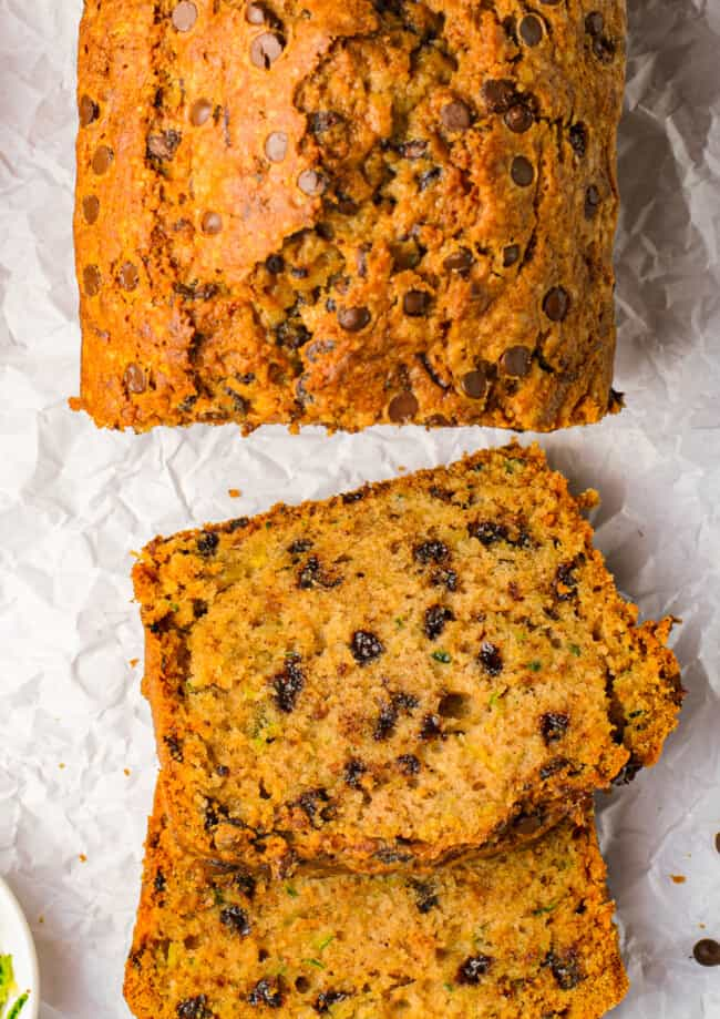 up close overhead sliced chocolate chip zucchini bread on white parchment