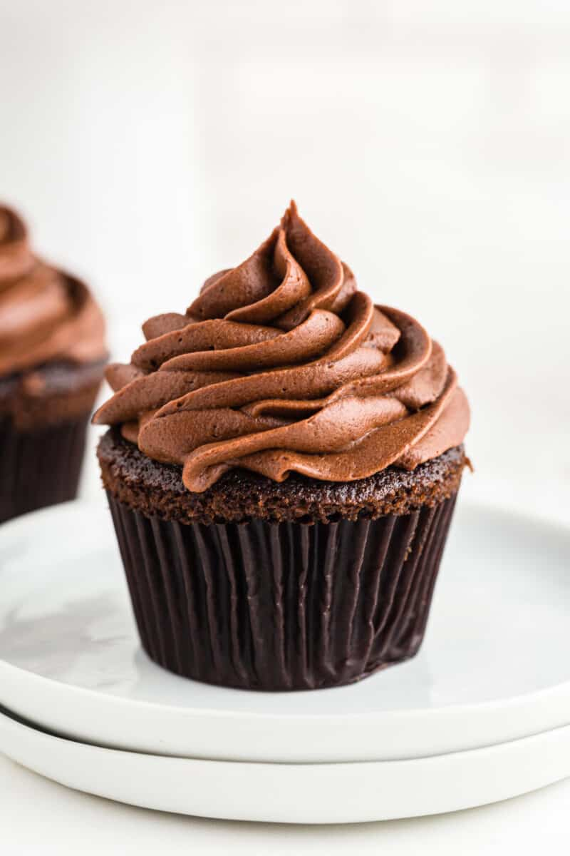 chocolate cupcake with chocolate buttercream frosting on white plate