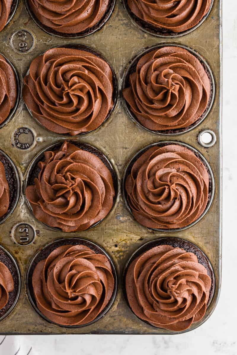 overhead chocolate cupcakes with chocolate buttercream in cupcake tin