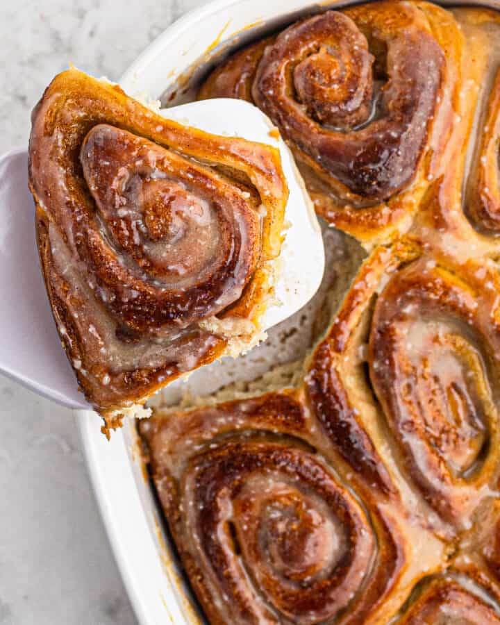 holding up cinnamon roll with serving spatula