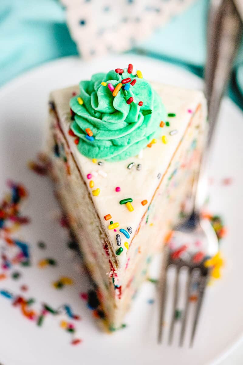 slice of funfetti cake with green frosting on white plate