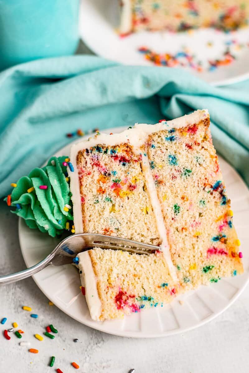 fork digging into slice of funfetti cake