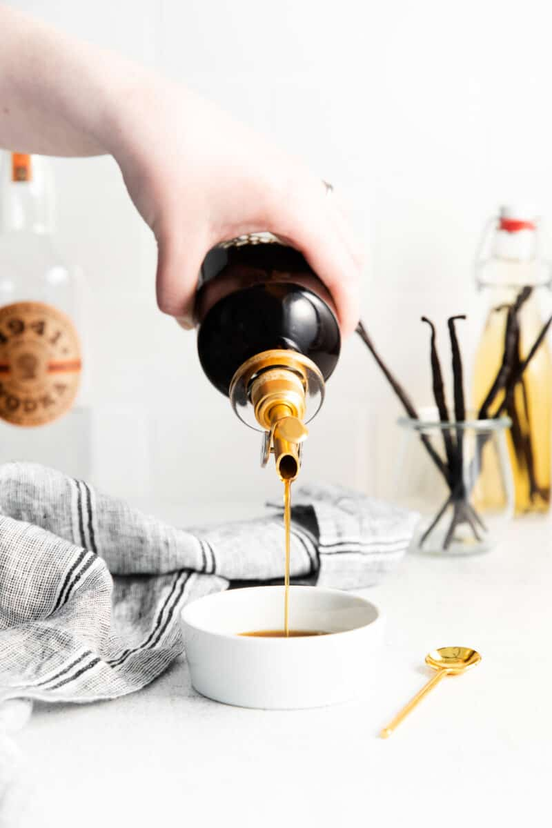 pouring vanilla extract into dish