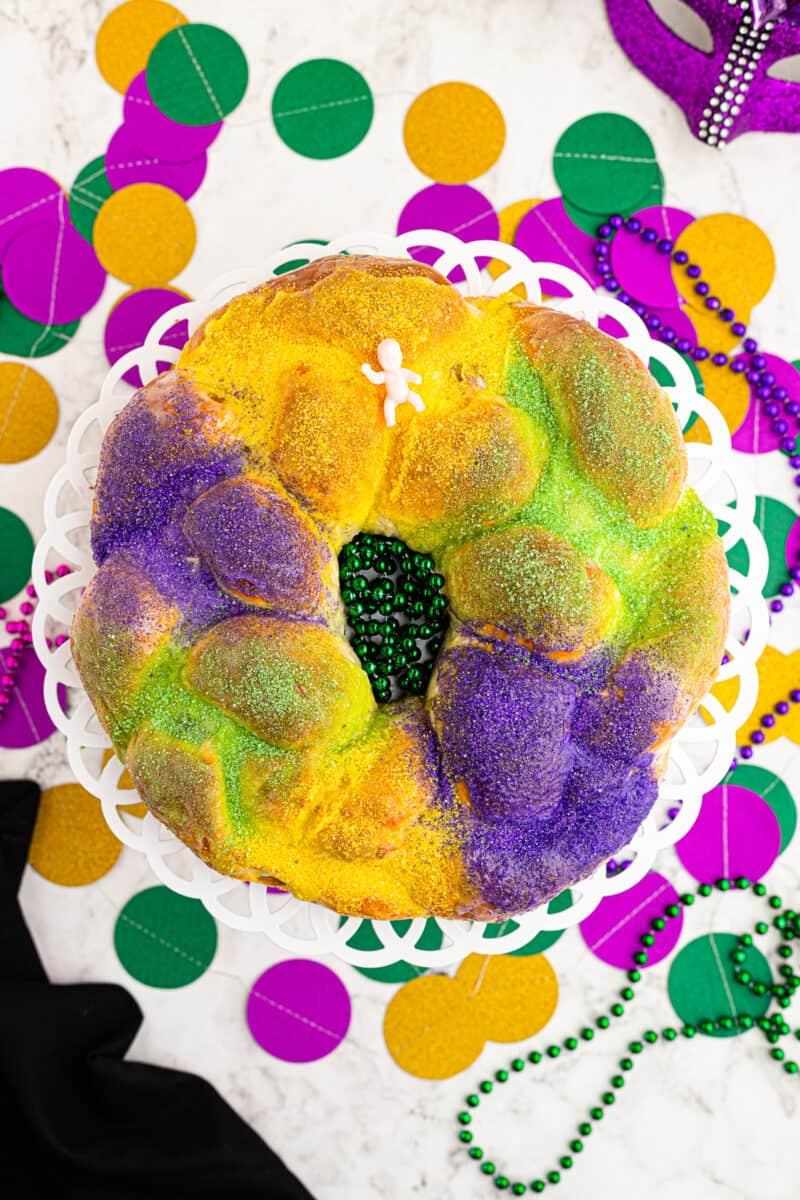 king cake sitting amongst mardi gras decorations