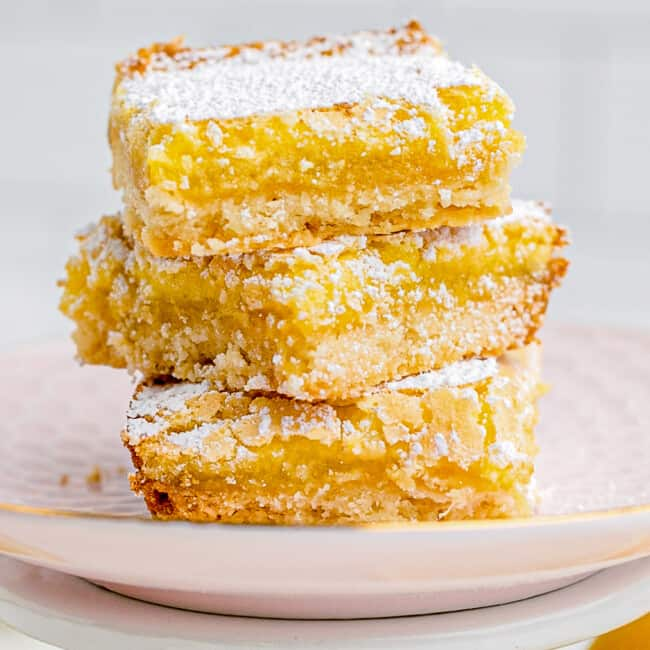 stacked lemon bars on pink plate
