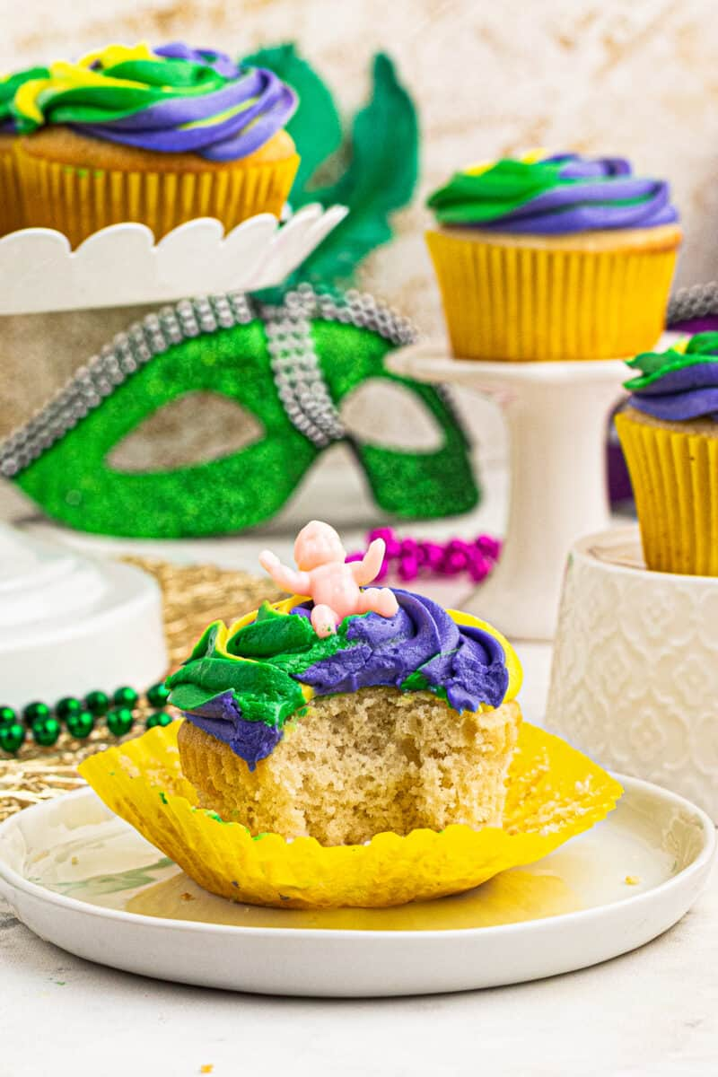 bite out of mardi gras cupcake with baby among mardi gras decorations