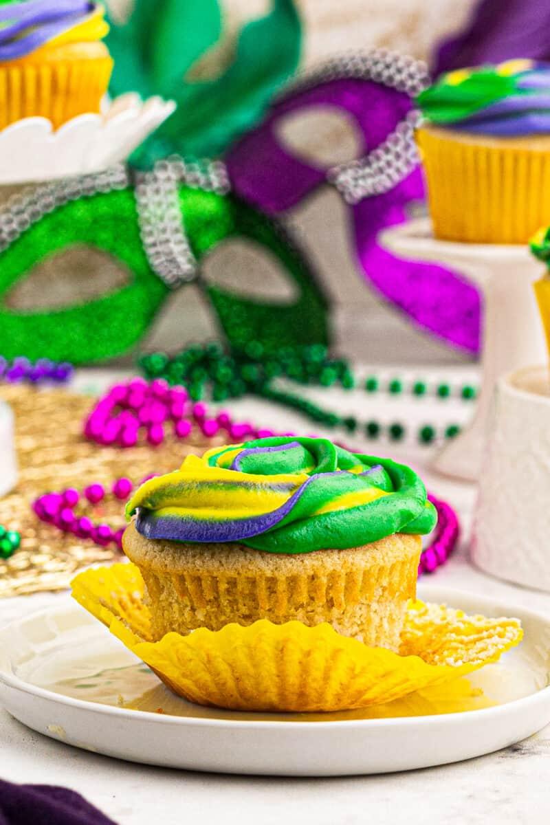 mardi gras cupcake next to mardi gras decorations