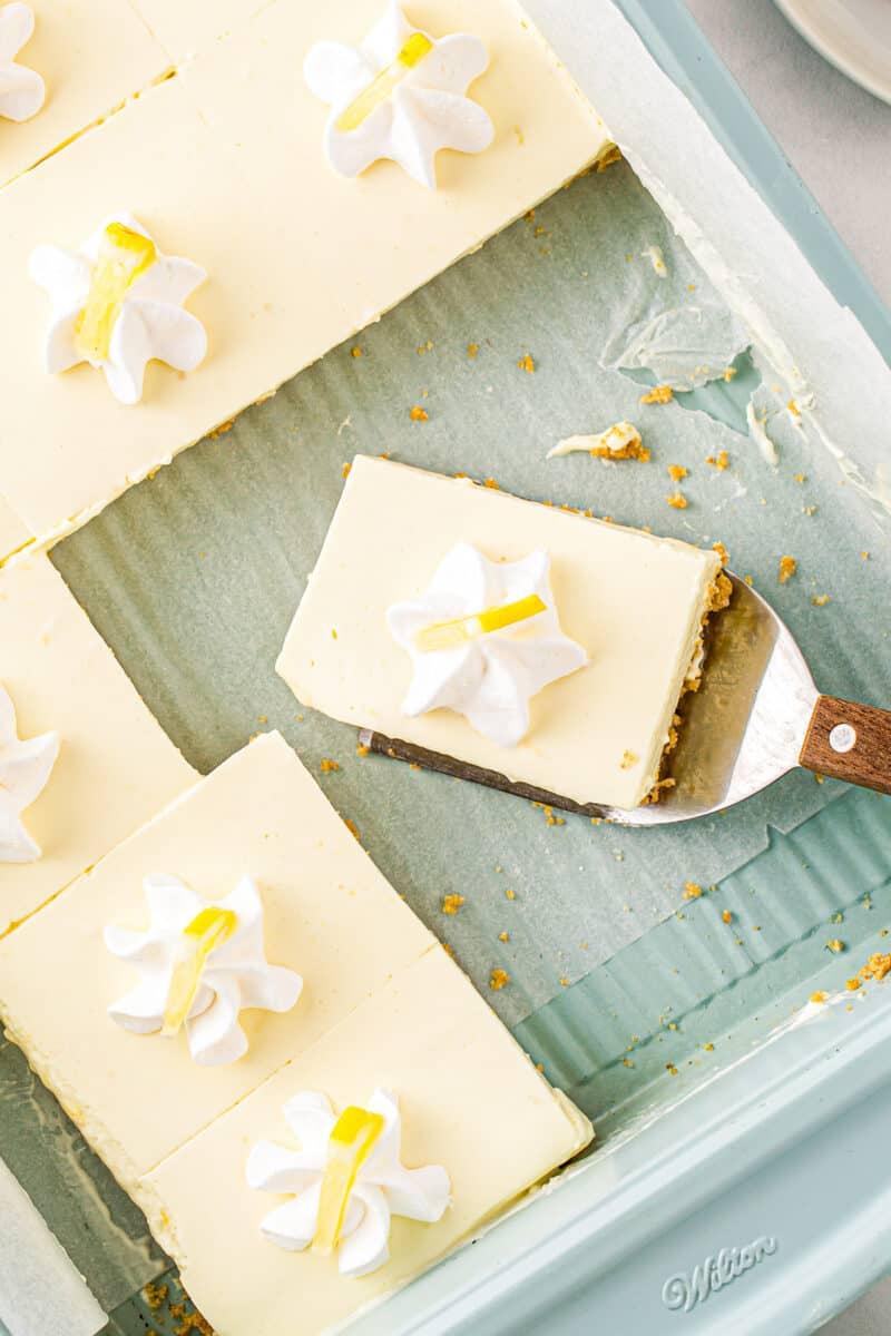 sliced no bake lemon cheesecake with whipped cream garnish