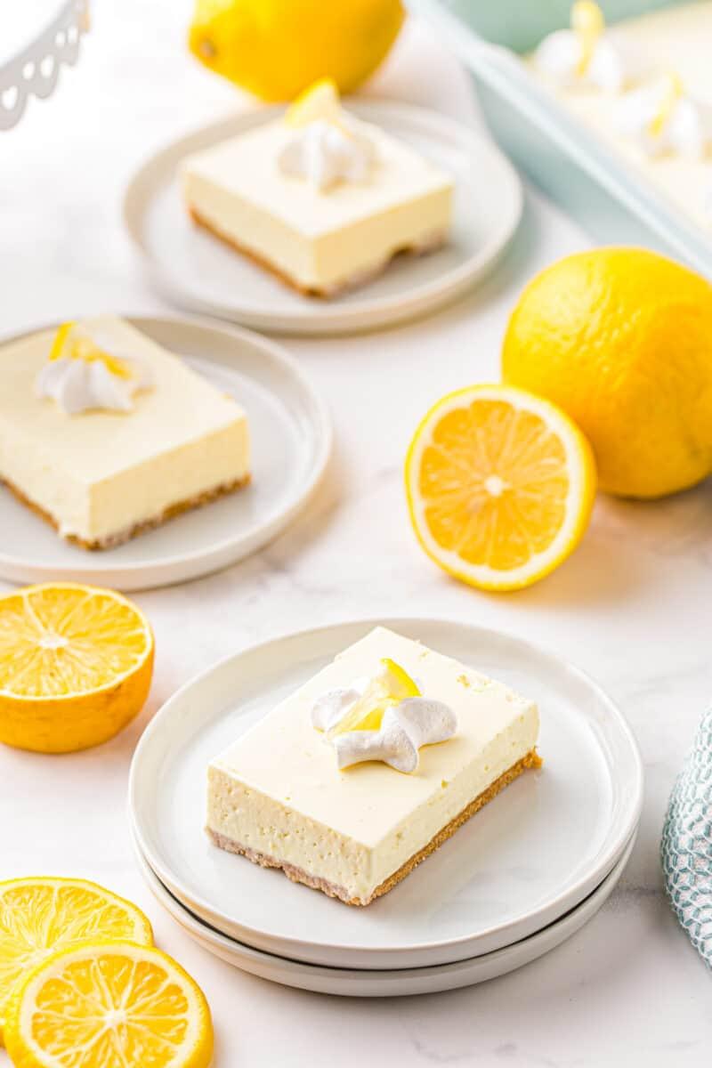 3 slices of no bake lemon cheesecake on white plates
