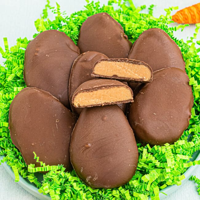 homemade reese's peanut butter eggs over fake grass with one cut in half