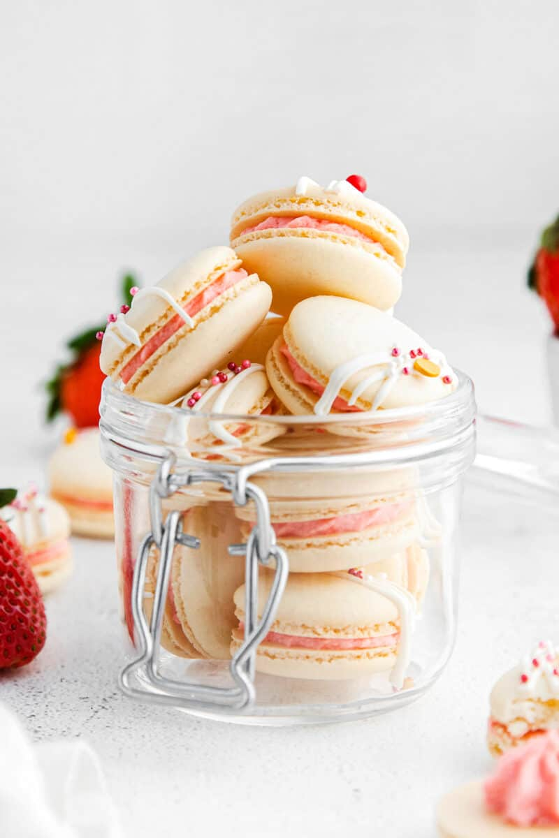 up close strawberry macarons in clear bowl
