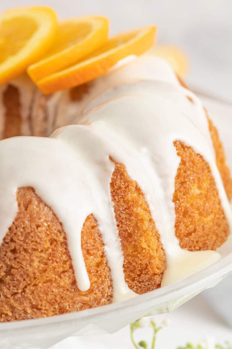 iced orange bundt cake on cake stand