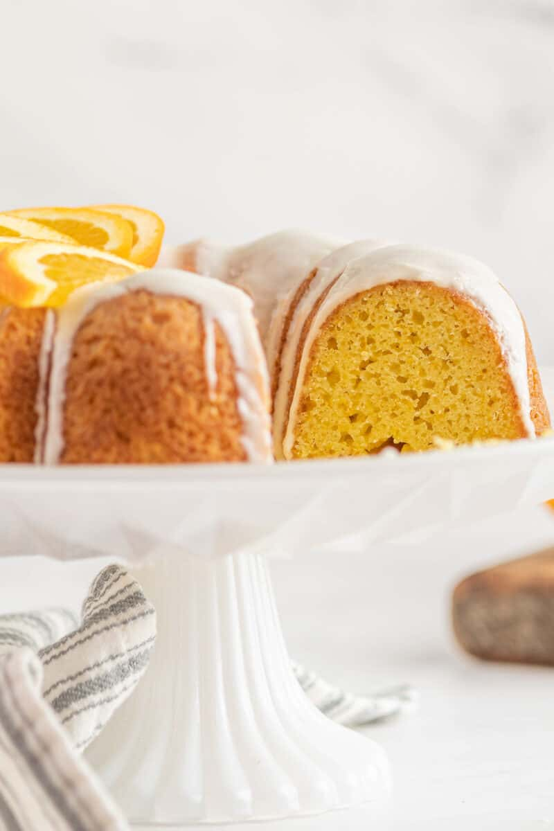 iced orange bundt cake on cake stand sliced