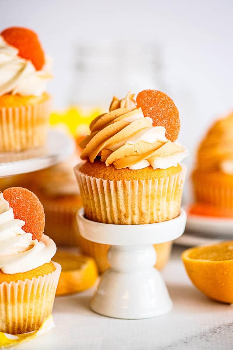 orange creamsicle cupcakes on cake stand