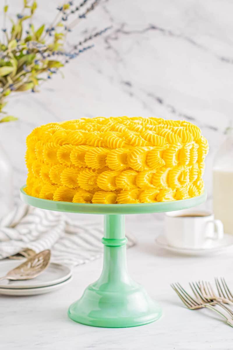 iced mango cake on a cake stand