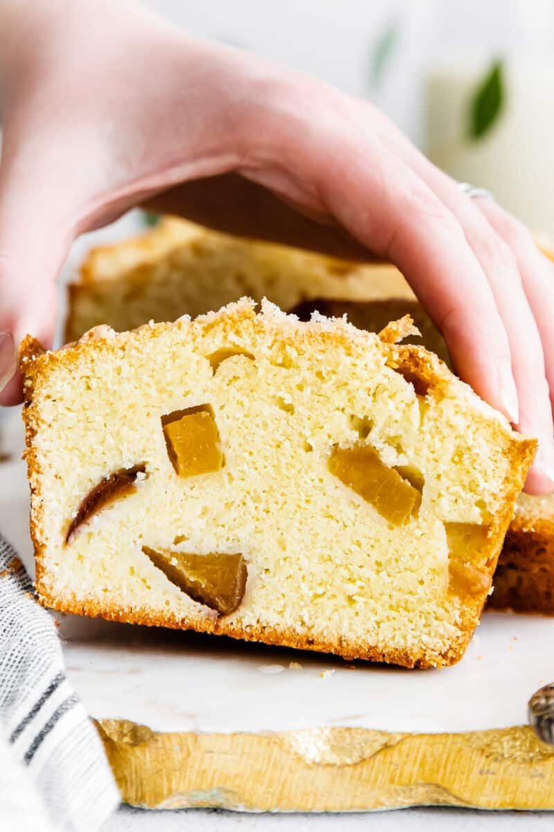 holding slice of fresh peach pound cake