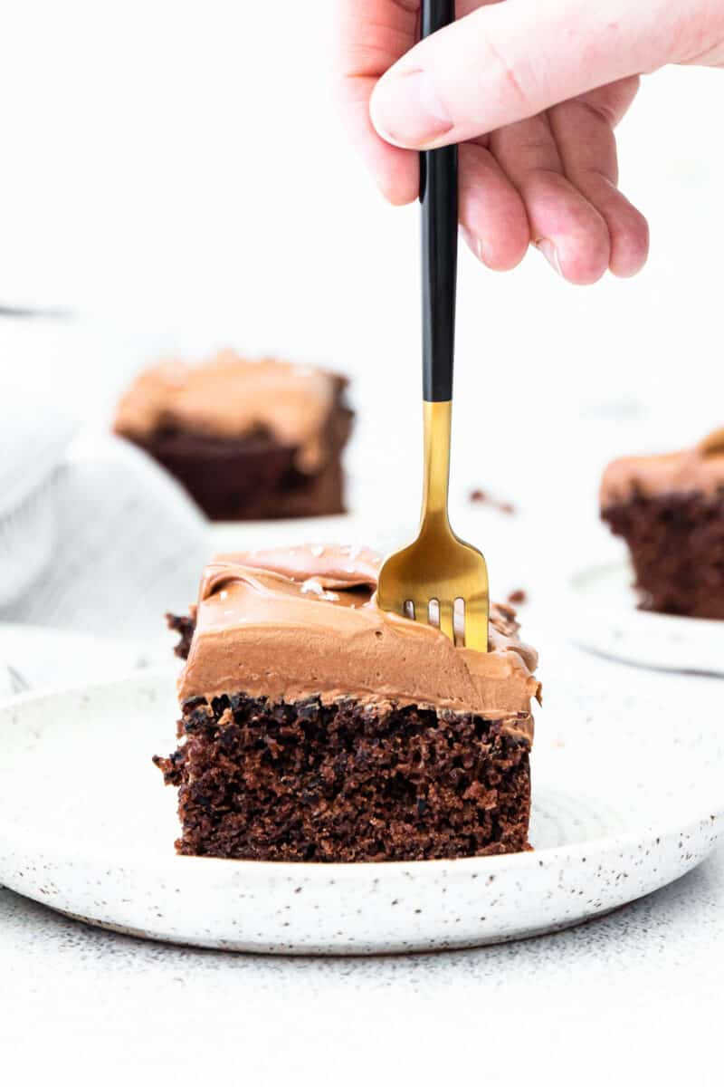 fork in slice of double chocolate cake on white plate