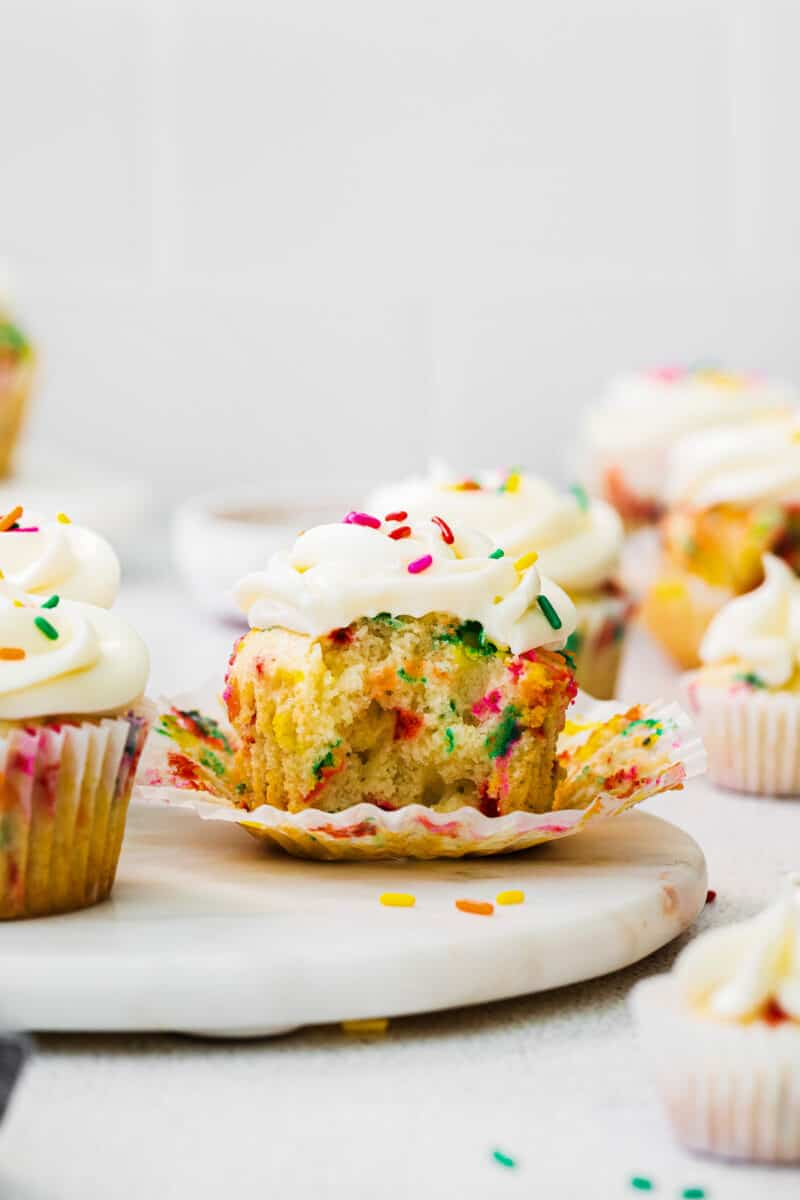 bite out of funfetti cupcake with frosting and sprinkles