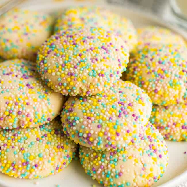 stacked sprinkle cookies on white plate