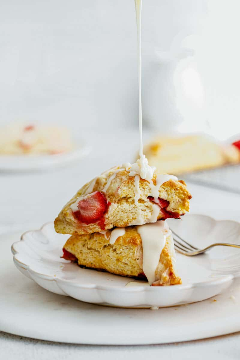 drizzling white glaze on fresh strawberry scones