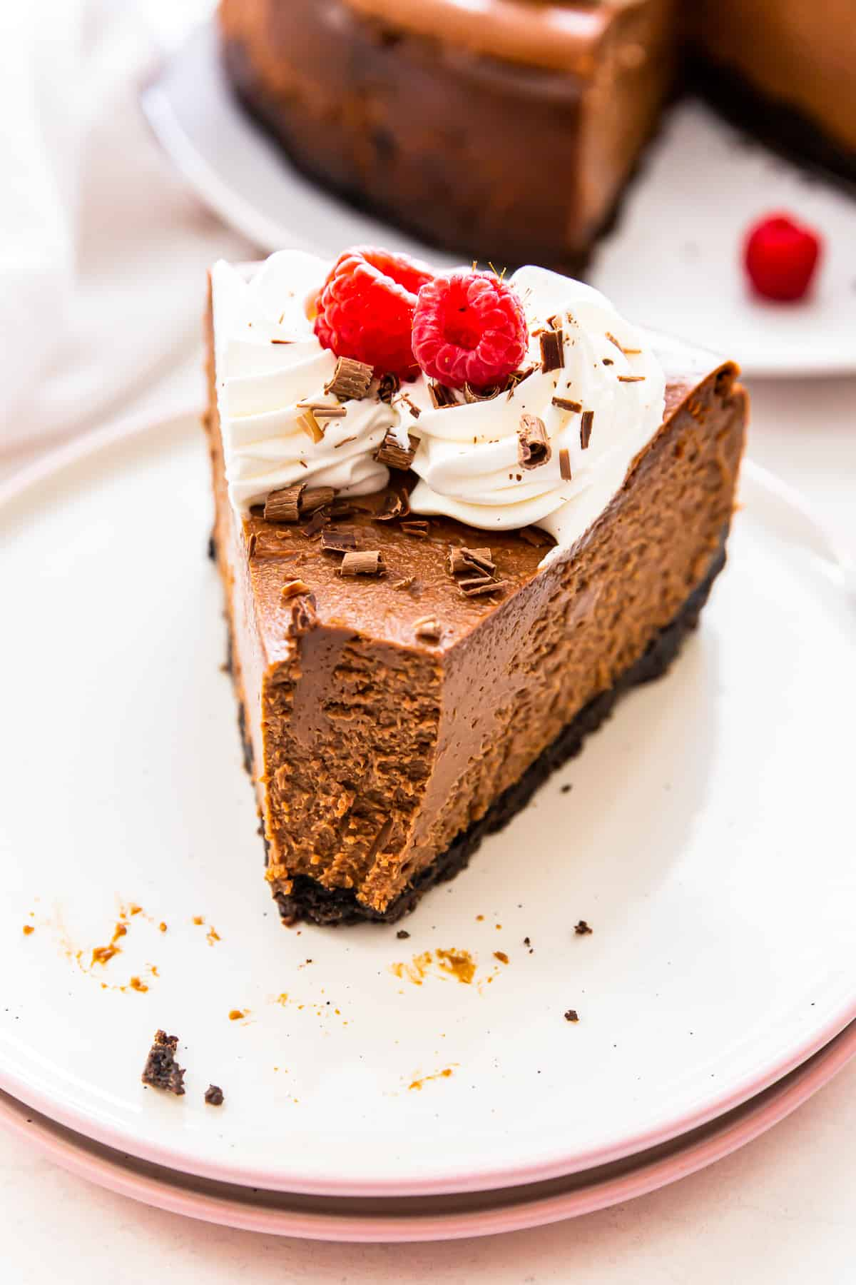 slice of chocolate cheeesecake on white plate with bite out