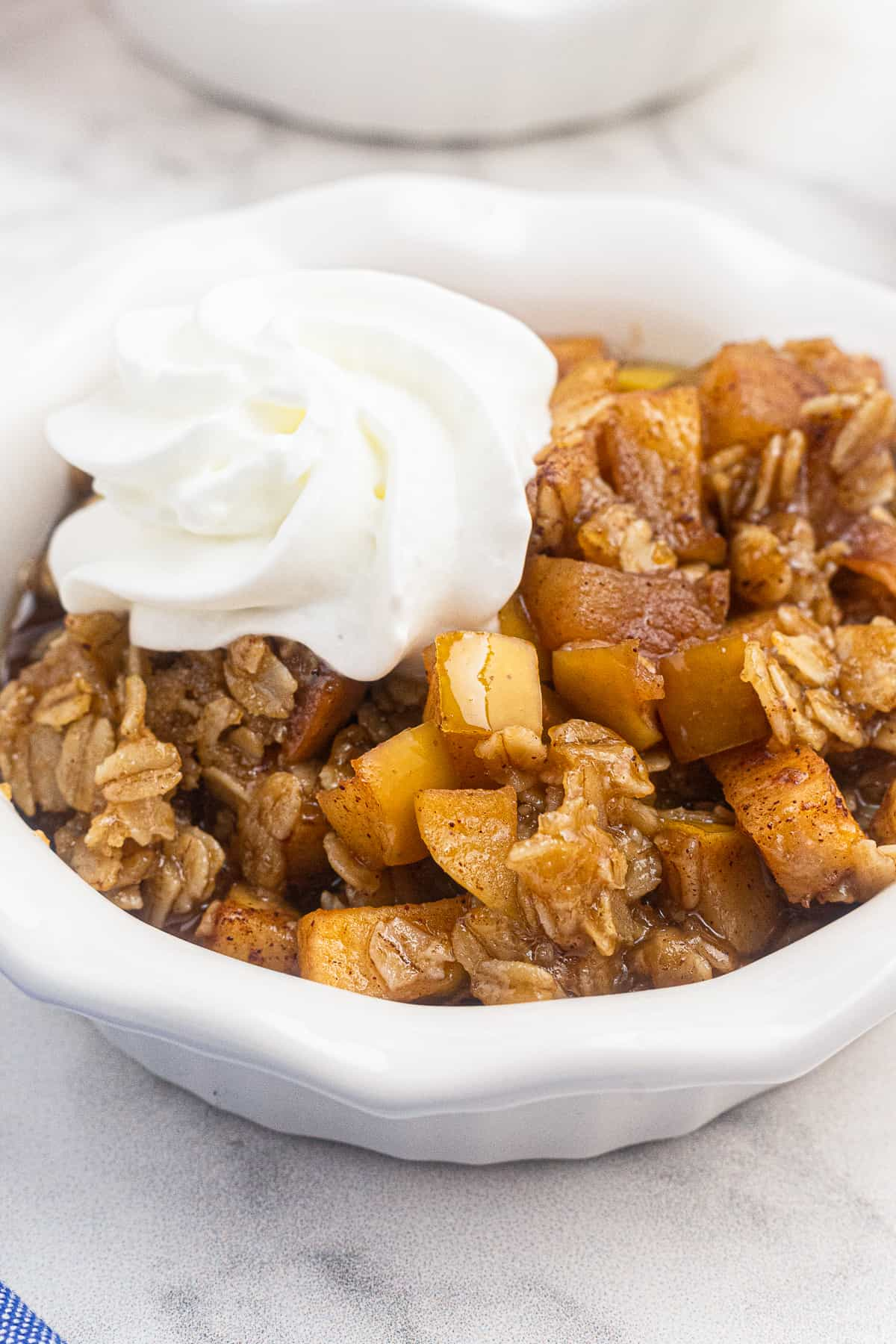 up close bowl of instant pot apple crisp with whipped cream