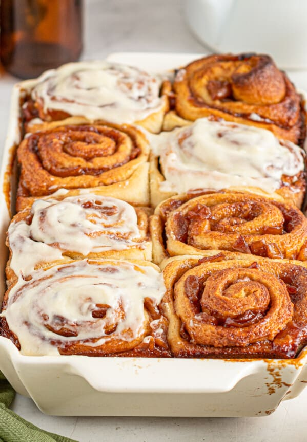 apple pie cinnamon rolls with frosting in pan