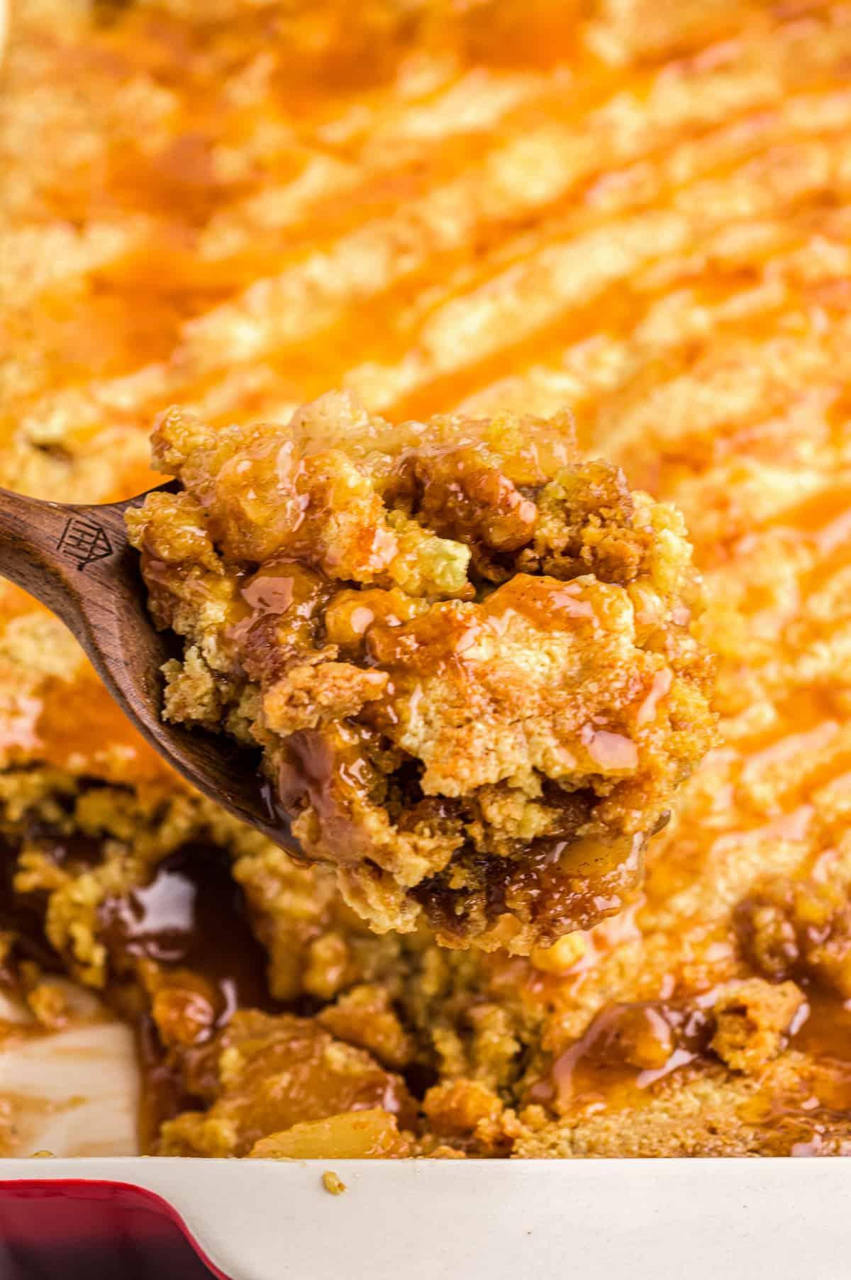 lifting up spoonful of caramel apple dump cake