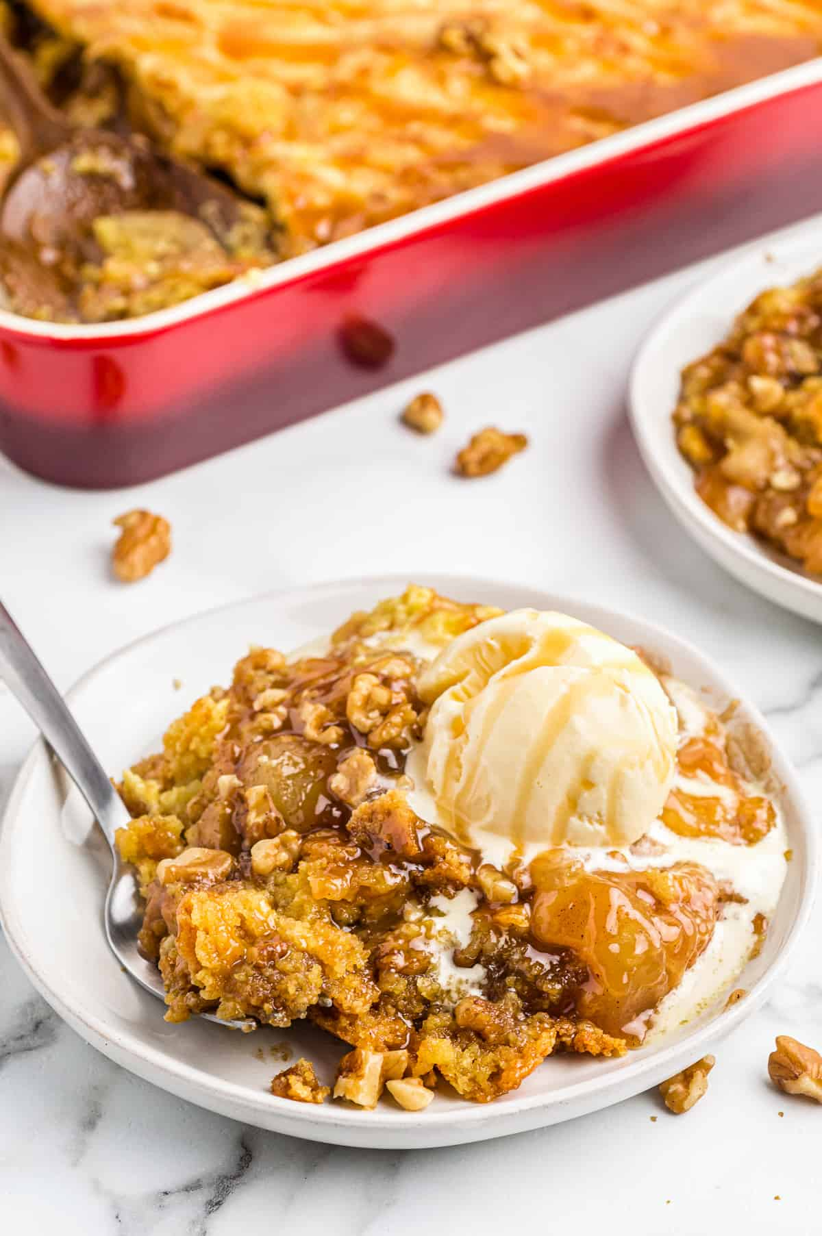 white plate with caramel apple dump cake and ice cream