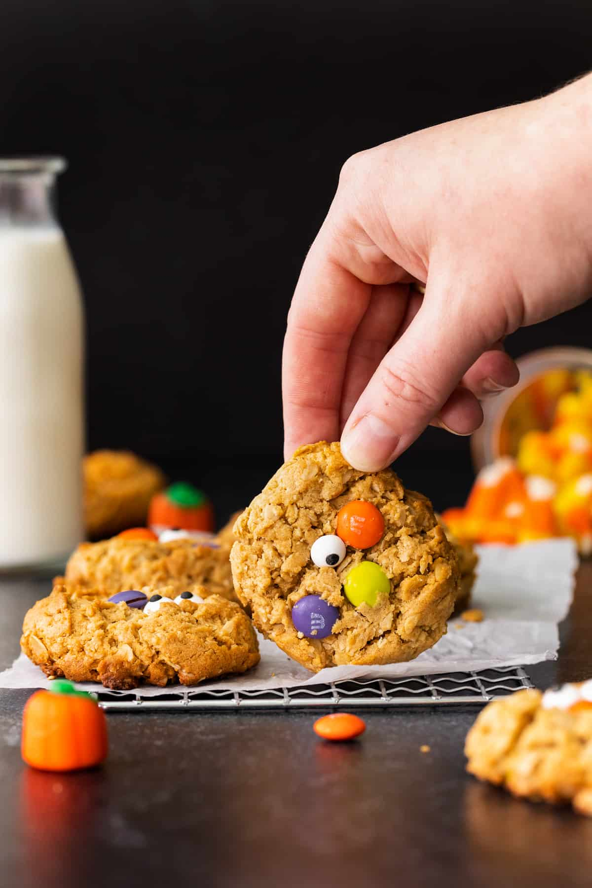holding up halloween monster cookie with m&ms