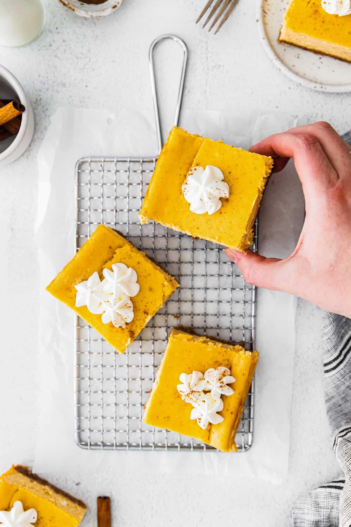 pumpkin cheesecake bars on cooling rack