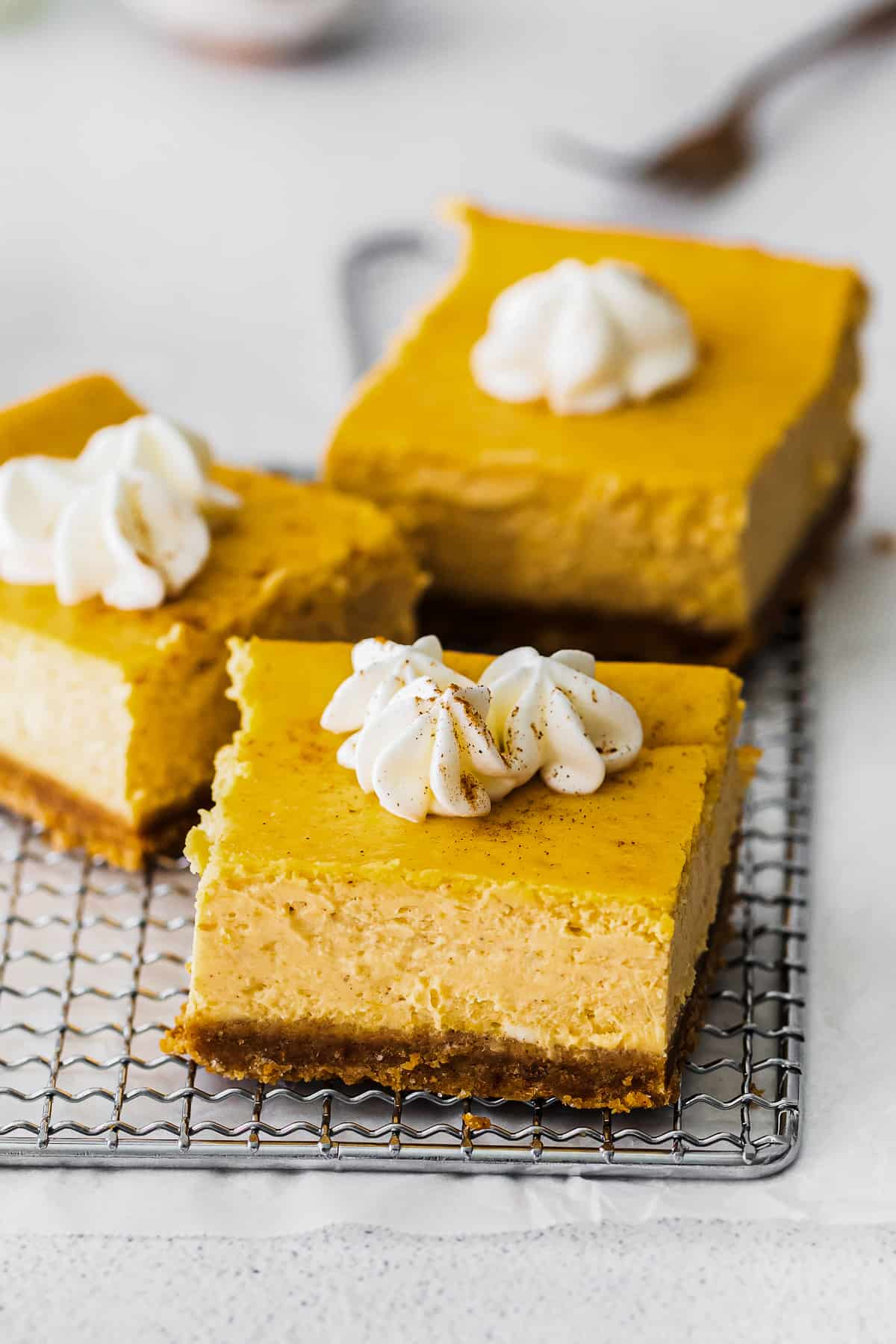 up close pumpkin cheesecake bars with whipped cream