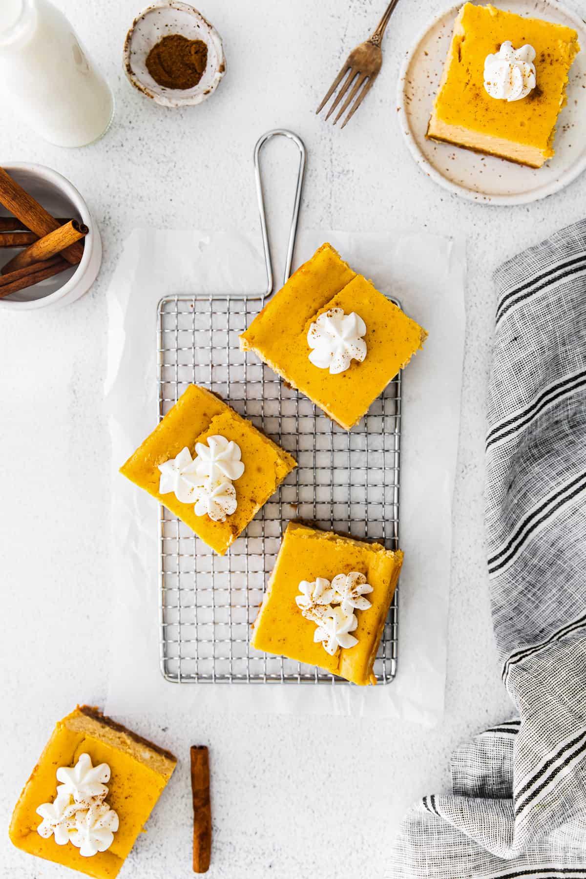 three pumpkin cheesecake bars with graham cracker crust
