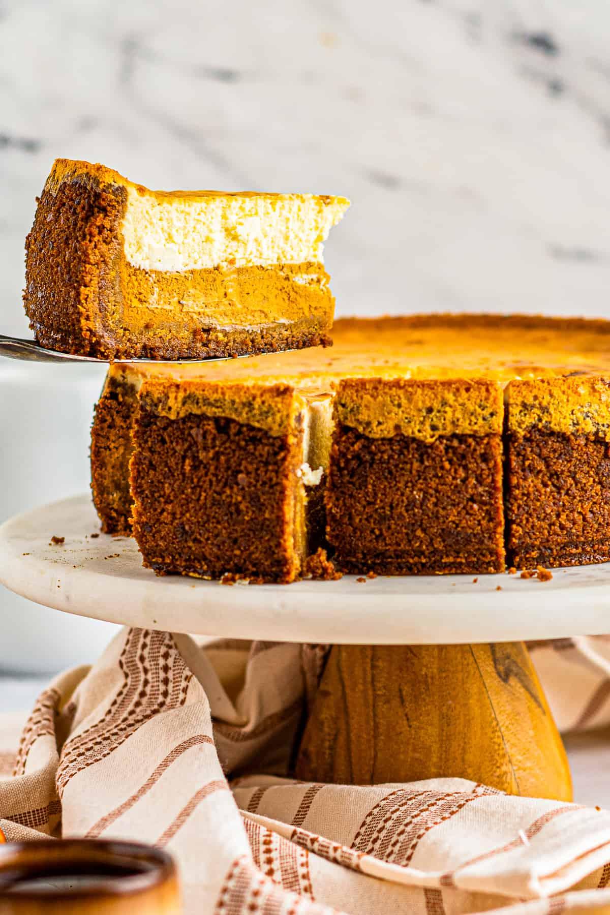 lifting up slice of pumpkin pie cheesecake
